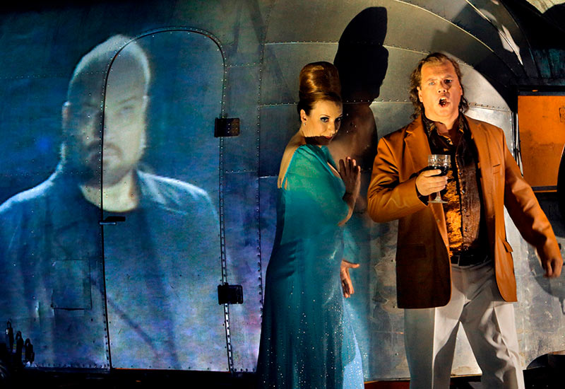 Stefan Vinke (Siegfried) and Alison Oakes (Gutrune). To the left, on video, Hagen (Stephen Milling) is watching. Photo: Enrico Nawrath / Bayreuther Festspiele